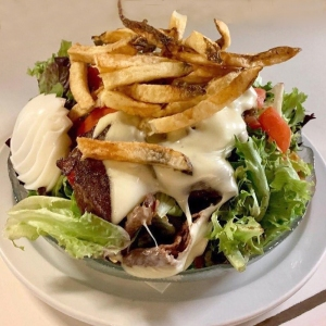 Stacked Salad topped with Fries